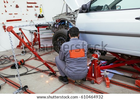 Auto mechanic changing wheels on car.