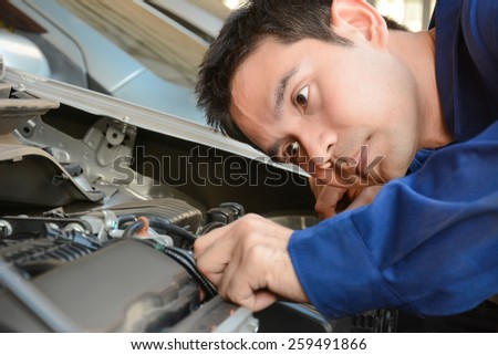 Auto mechanic checking car engine - face focused - stock photo