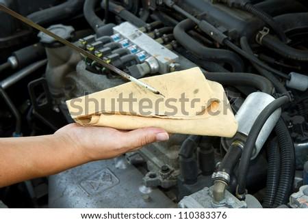 Auto mechanic checking oil - stock photo
