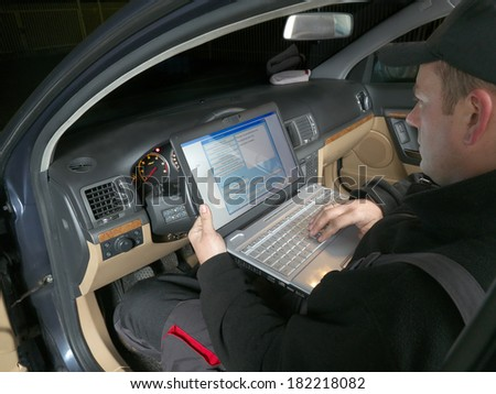Auto mechanic checking vehicle identification number of the car using laptop hooked up to the car onboard computer - stock photo