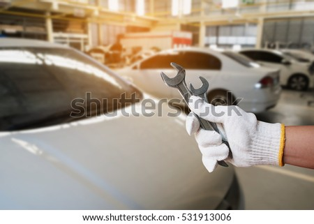 Auto mechanic hand holding wrench over car repair service centre garage