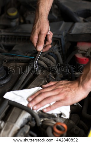 Auto mechanic hand with wrench close up