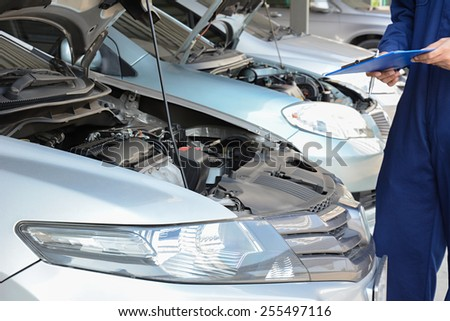 Auto mechanic (or technician) checking car engine at the garage - stock photo