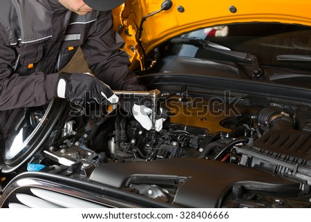 Auto Mechanic performing maintenance on the engine - stock photo