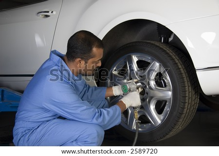 Auto mechanic removing wheel of a car in a workshop
