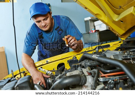 auto mechanic repairman tighten screw with spanner during automobile car maintenance at engine repair service station garage - stock photo