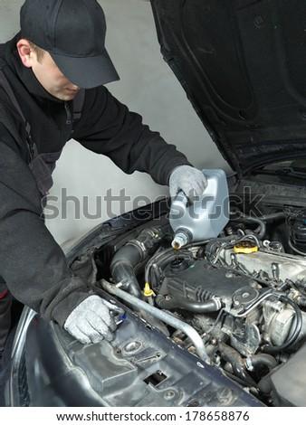 Auto mechanic replenishing engine oil  - stock photo
