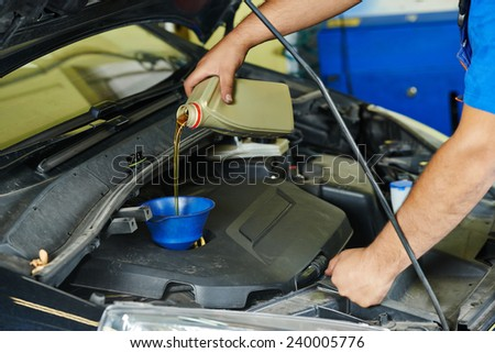 auto mechanic technician replacing and pouring motor oil into automobile engine at maintenance repair service station - stock photo