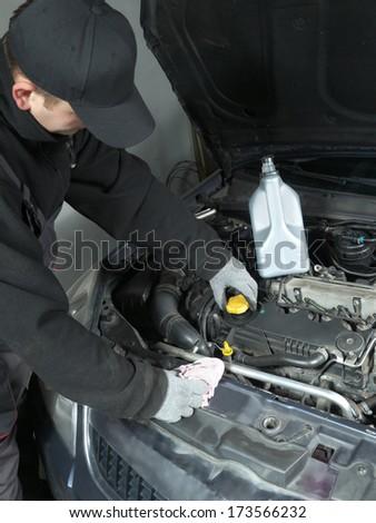 Auto mechanic unscrewing oil filler cap - stock photo