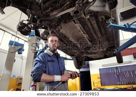 auto mechanic with a wrench under a car - stock photo