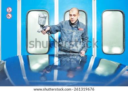 auto mechanic worker priming a car bonnet before painting in a chamber during repair work - stock photo
