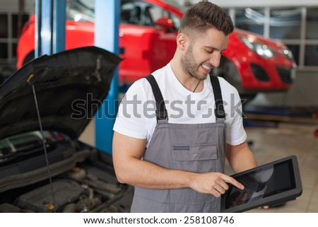 Auto mechanic working on a digital tablet. Smiling man in workshop working on a digital tablet. - stock photo