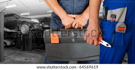 Auto mechanics closeup over workshop background - stock photo