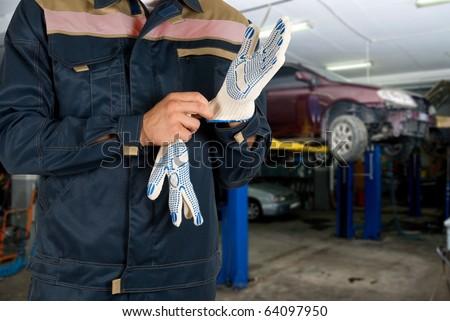 Auto mechanics closeup standing in his workshop - stock photo