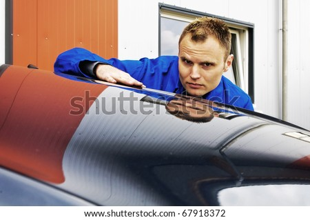 Auto Mechanics sweeps his hand over a car and checked the paint in front of the garage, his face is reflected in the paint - stock photo