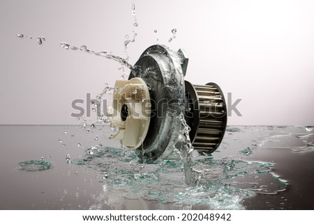 Auto parts, engine cooling pump in spurts of water on a light gradient background - stock photo