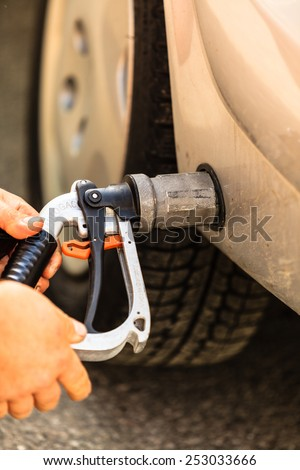 Auto refuel. Car at gas station being filled with fuel, fill up of liquefied petroleum gas, LPG