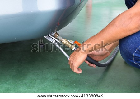 Auto refuel. Car at gas station being filled with fuel, fill up of liquefied petroleum gas, LPG. - stock photo