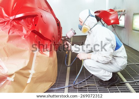auto repair worker painting a red car in a paint chamber during repair work - stock photo