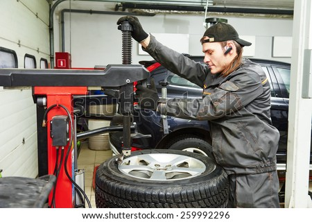 Auto repairman loading automobile car wheel at tyre fitting machine during tire replacing - stock photo