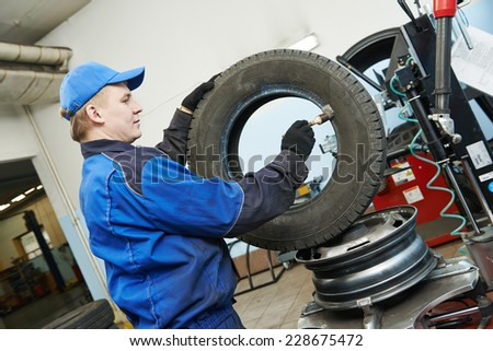 Auto repairman lubricating automobile car wheel during tyre fitting or tire replacing - stock photo