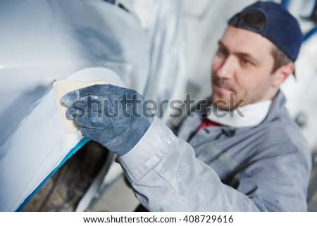 auto repairman plastering autobody bonnet  - stock photo