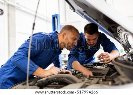 auto service, repair, maintenance and people concept - mechanic men with wrench repairing car engine at workshop