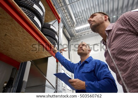 auto service, repair, maintenance and people concept - mechanic with clipboard and man looking at tires at car shop