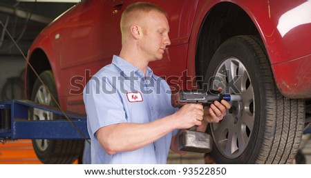 Auto shop mechanic working on car wheel - stock photo
