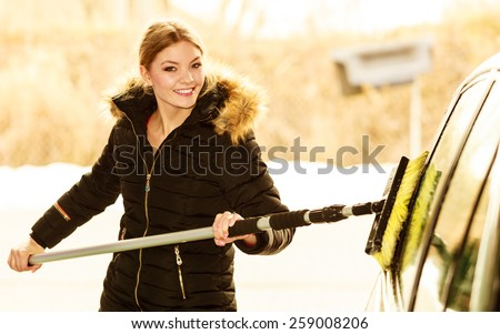 Auto wash. Young attractive blonde woman washing the dirty car on open air - stock photo