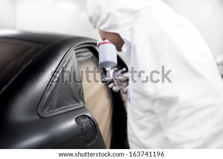 auto worker spraying black paint on a car in an auto garage