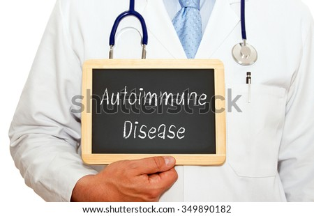 Autoimmune Disease - Doctor holding chalkboard with text on white background - stock photo