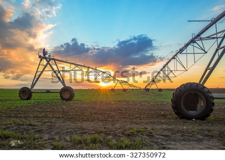 Automated farming irrigation sprinklers system on cultivated agricultural landscape field in sunset - stock photo