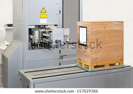 Automated labeling machine at production line in factory - stock photo
