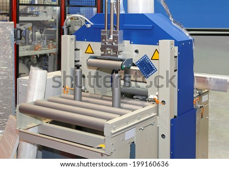 Automated machine for packing gods in foil - stock photo