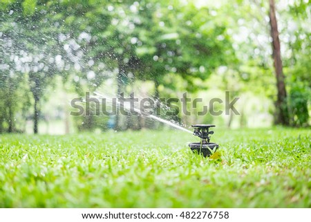 Automatic Garden Sprinkler Action Watering Grass Stock Photo