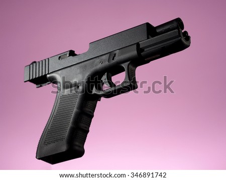 automatic hand gun on pink background, unloaded position - stock photo