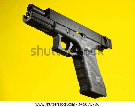 automatic hand gun on yellow background, unloaded position - stock photo