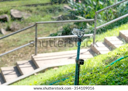 Automatic lawn sprinkler in the park. - stock photo