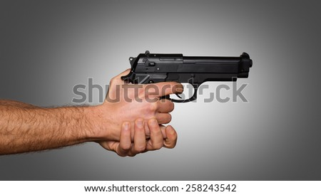 Automatic pistol handled with two hands - grey gradient background - stock photo