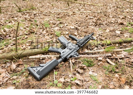 Automatic rifle m16 lying on the ground in the forest  - stock photo