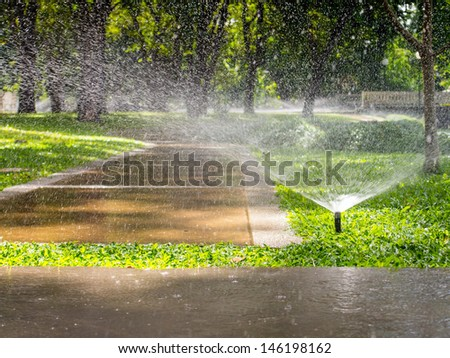 Automatic sprinkler watering in the garden - stock photo