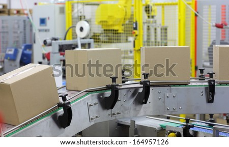 automation - Cardboard boxes on conveyor belt in factory - stock photo