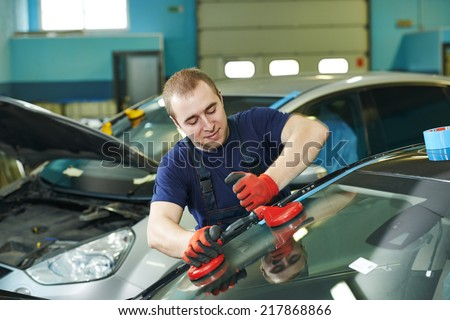Automobile glazier adding glue on windscreen or windshield of a car in auto service station garage before installation - stock photo