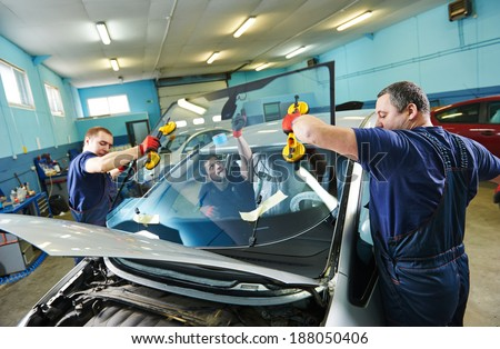 Automobile glaziers workers replacing windscreen or windshield of a car in auto service station garage - stock photo