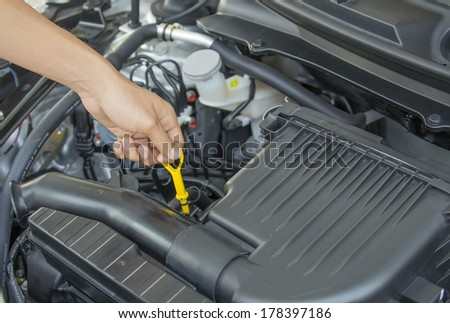 Automobile Maintenance - Pulling the Engine Dipstick to Check the Oil Level