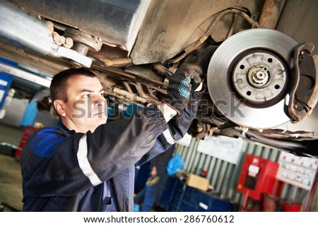 automobile mechanic inspecting car wheel brake disc and shoes of lifted automobile at repair service station - stock photo