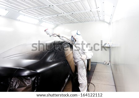 Automotive industry - engineer painting and working on a black body of a car and wearing protective gear - stock photo