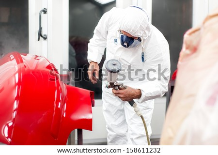 Automotive industry - engineer painting and working on a red body of a car