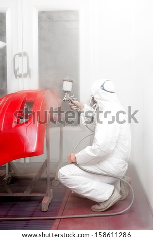Automotive master engineer painting a red car in a special booth
